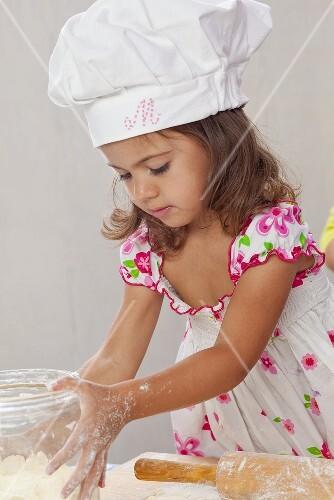 Small girl making dough