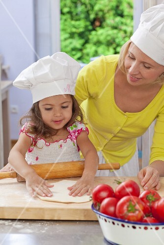 A mother and daughter making a pizza