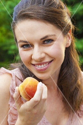 Young woman with a yellow peach