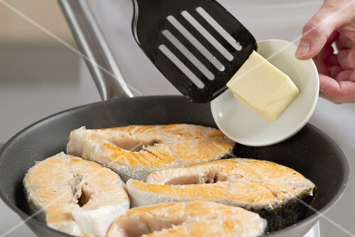 Butter being added to a pan of salmon steaks