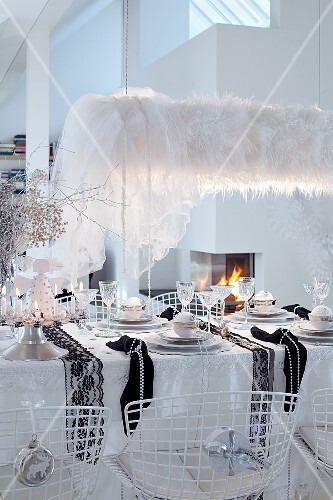 A dining table decorated for Christmas in black and white