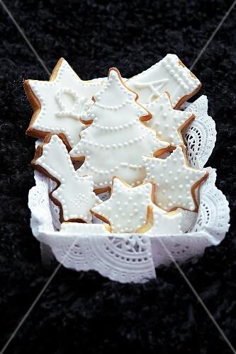 Mürbteigplätzchen mit weissem Zuckerguss auf Tortenpapier