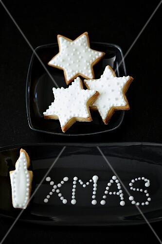 Mürbteigplätzchen (Sterne, Kerze) mit weisser Glasur