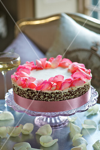 A wedding cake with rose petals