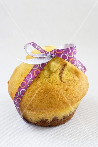 A chocolate and vanilla muffin tied with a bow