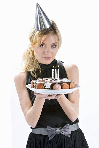 A blonde woman holding a birthday cake