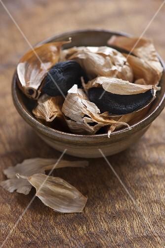 Black garlic, semi peeled, in a ceramic bowl