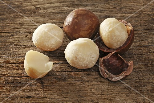 Macadamia nuts, with and without shells on a wooden surface