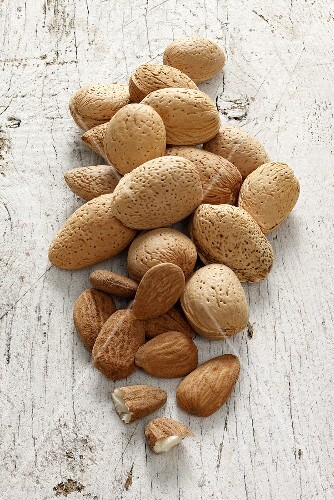 Almonds with and without shells on a white wooden surface