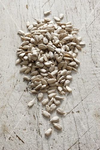 Sunflower seeds on a white wooden surface