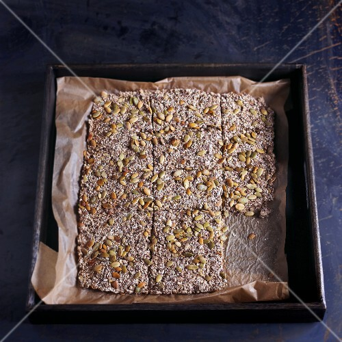 Home made whole grain crackers with seeds on a baking sheet