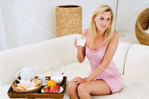 Young woman eating breakfast in living room