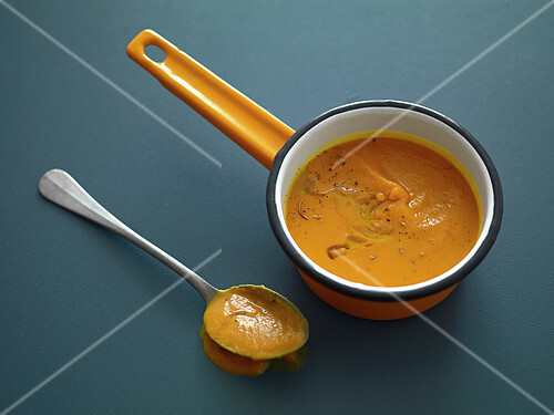 Saucepan and large spoonful of pumpkin soup