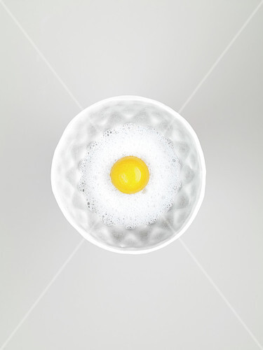 Raw egg yolk in egg white emulsion in a bowl