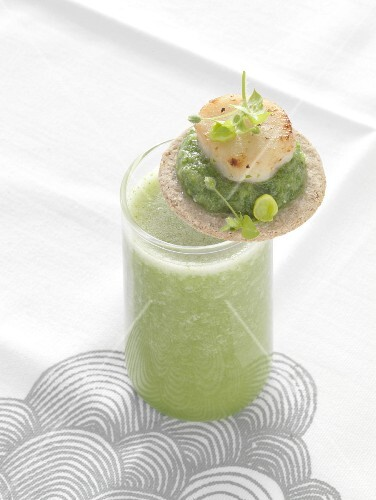 Green gazpacho with a cracker garnished with mashed peas and scallops