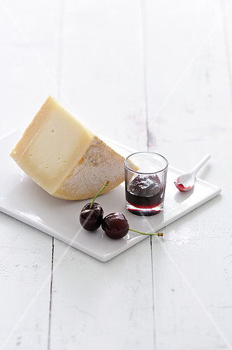 Portion of sheep's milk cheese and black cherry jam