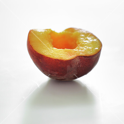 Half a peach on a white background