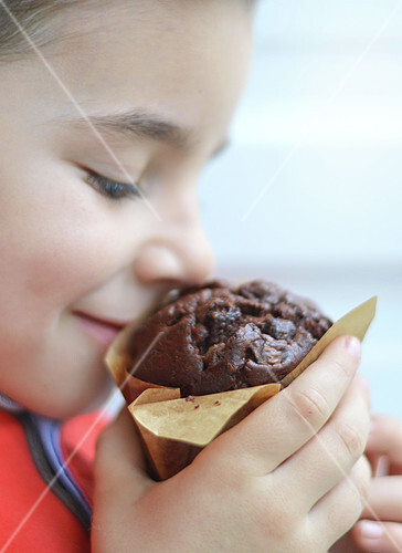 Child smelling a chocolate muffin