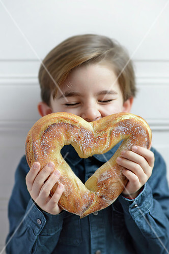 Child kissing a heart-shaped bread