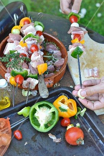 Preparing pork and vegetable brochettes on the barbecue