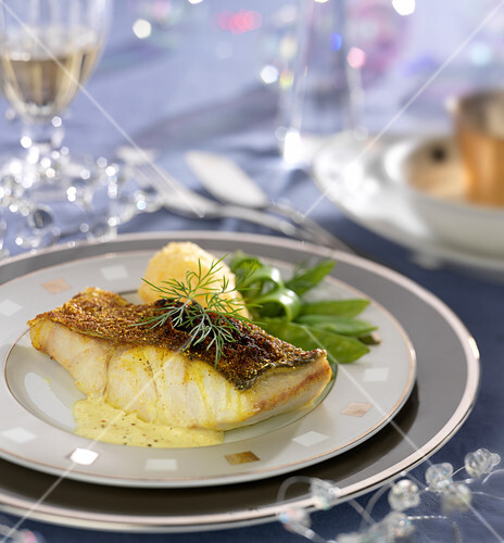 Piece of pollock in creamy curry sauce, rutabaga mash and sweet peas
