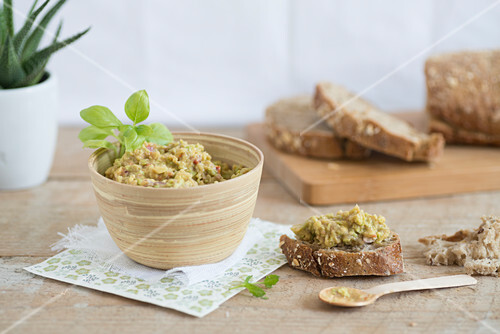 Bamboo bowl of guacamole and guacamole on sliced bread