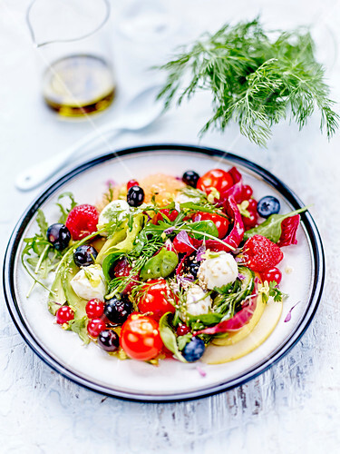 Avocado,cherry tomato,red fruit and mozzarella ball salad with olive oil