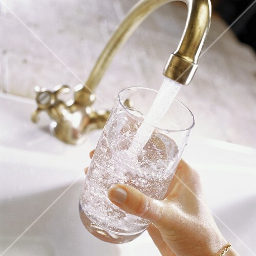 Glass of water under running tap