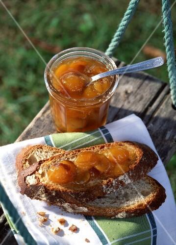 Jar of plum jam and plum jam on slices of bread
