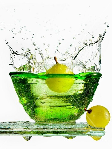 A grape falling into a fresh bowl of water