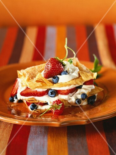 Layered cake made from filo pastry with cream and fruits of the forest