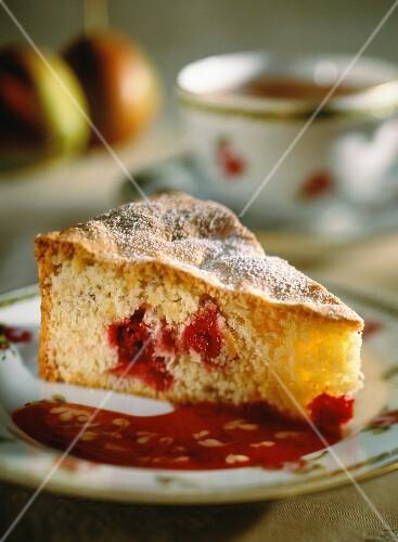 A slice of cherry sponge cake with cherry sauce