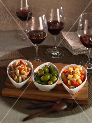 Various tapas and glasses of red wine