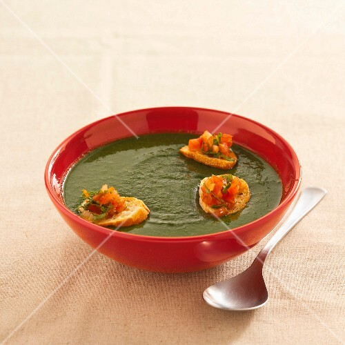 Cream of rocket soup with croutons topped with tomatoes