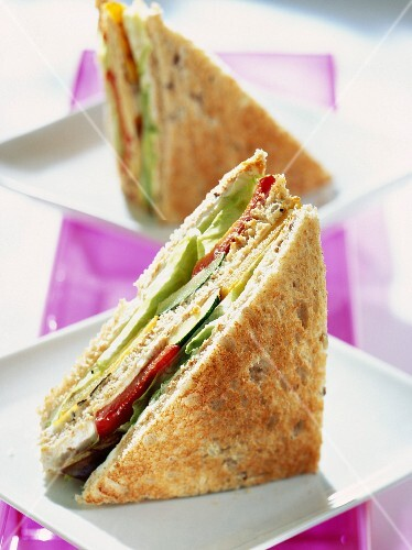 A club sandwich with peppers, lettuce and cheese