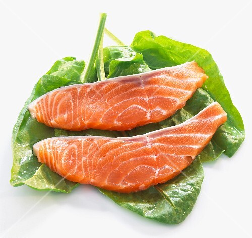 Raw salmon fillets with fresh spinach