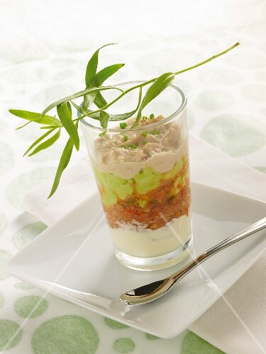 Tuna fish mousse, peas, tomatoes and cream in a glass