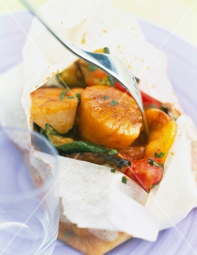 Scallops and vegetables cooked in wax paper