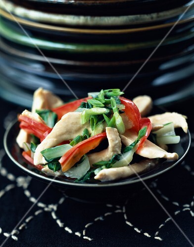 Sliced chicken breasts in cream with red peppers and Bok choy