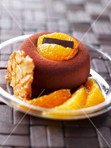 Small round cake coated with cocoa and fresh oranges