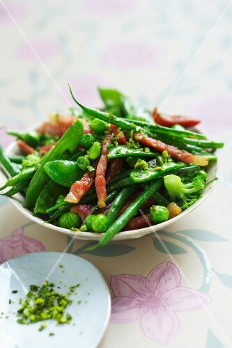 Green vegetable and thinly sliced pieces of ham cooked in a wok