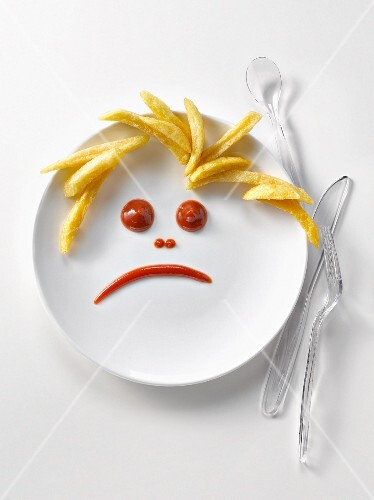 Plate of french fries and ketchup in the shape of a sad face