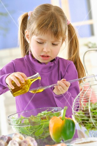 Young girl preparing the dressing for the salad