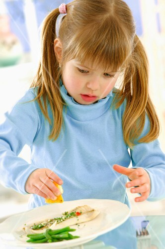 Young girl sprinkling lemon juice onto a plate of fish