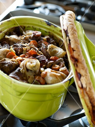 Beef,carrot and onion stew served in a casserole dish sealed with dough