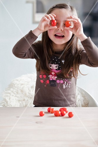 Young girl playing with cherry tomatoes