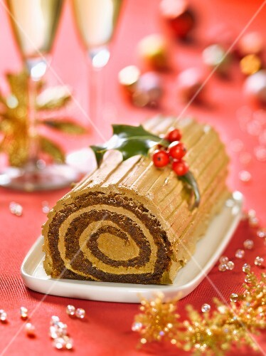 Christmas coffee log cake decorated with holly