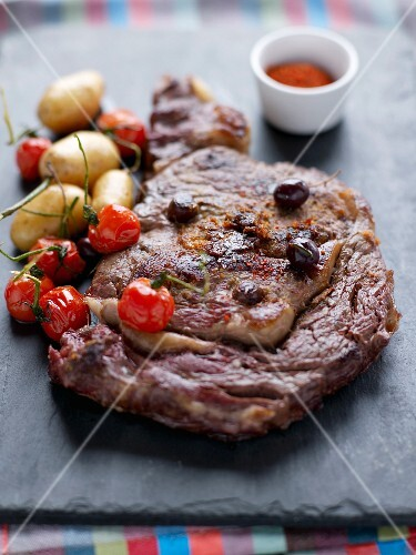 Grilled beef entrecôte with olives, cherry tomatoes and Ratte potatoes