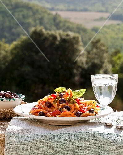 Plate of noodles with tomatoes and olives on a table outdoors