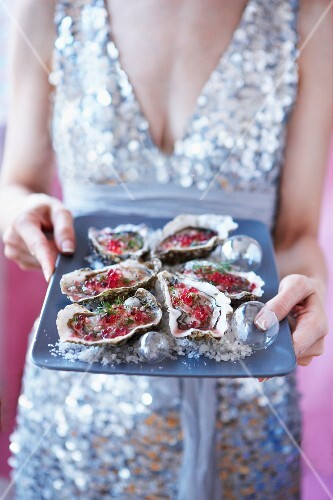Elegant woman serving fresh oysters with raspberry vinaigrette